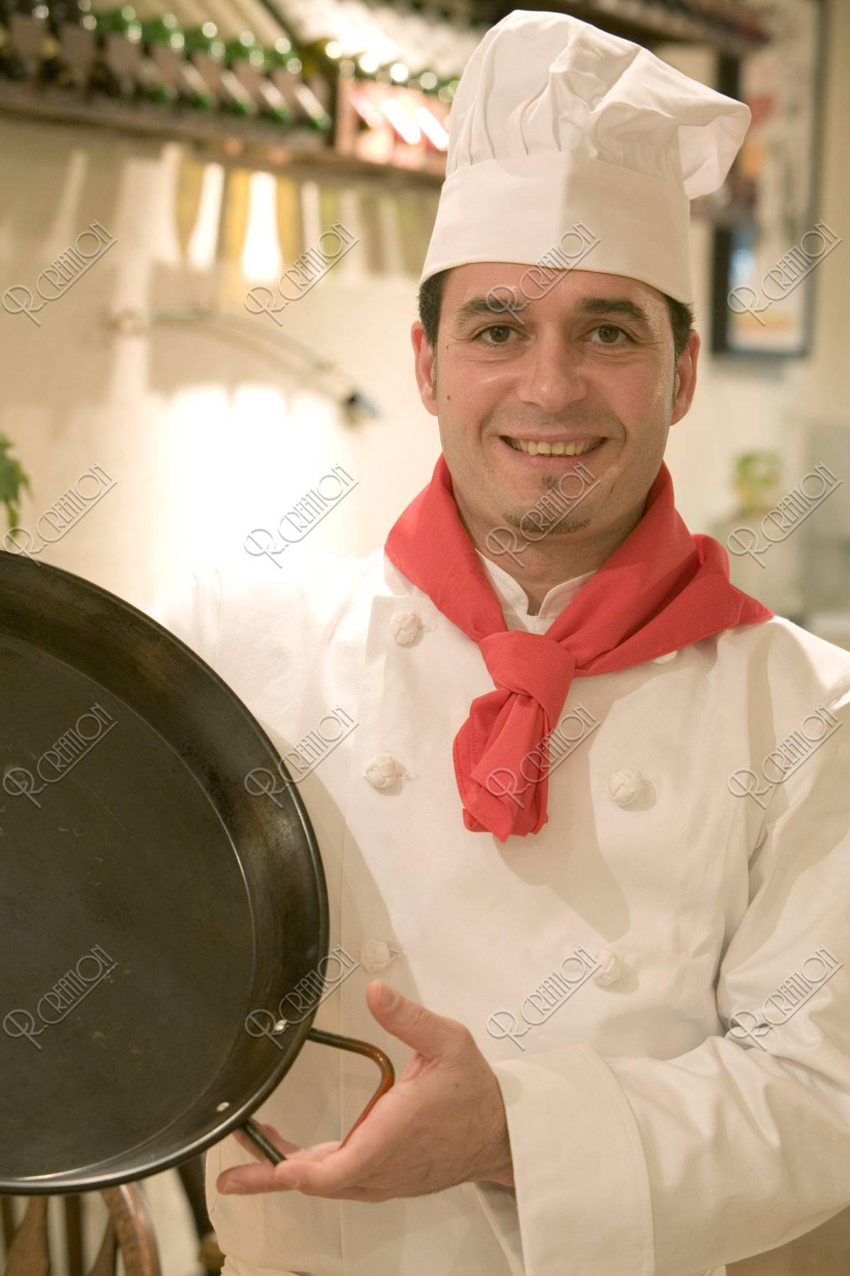 パエリャ鍋を持つシェフ