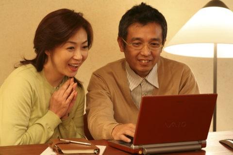 ノートパソコンを見る熟年夫婦