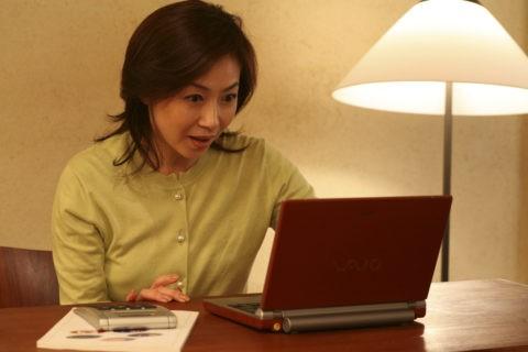 ノートパソコンを見る熟年女性
