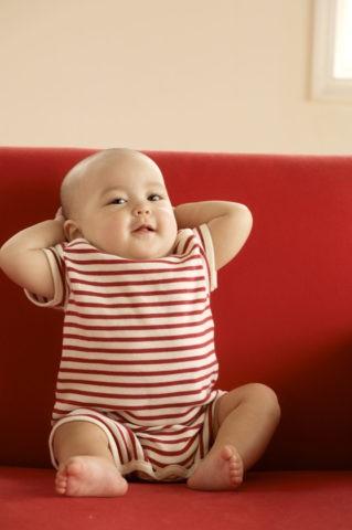赤ちゃん 白い帽子 赤いソファ