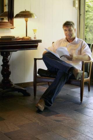 リビングで本を読む男性