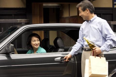 町家前の車と熟年夫婦