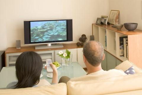 リビングで薄型テレビを見る熟年夫婦
