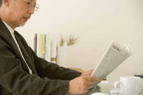 新聞を読む熟年男性