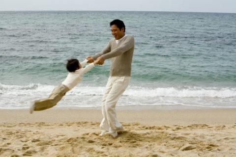 浜辺で遊ぶ父親と子供