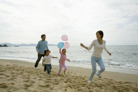 浜辺で風船で遊ぶファミリー