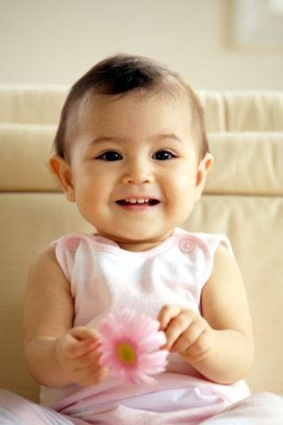ピンクの花を持つ赤ちゃん