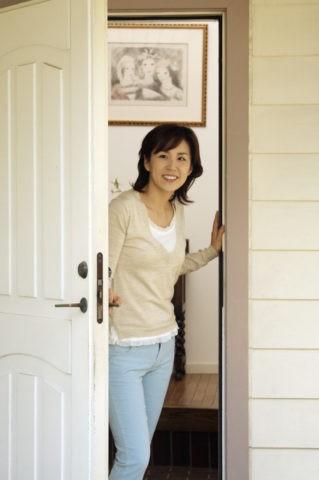 女性 笑顔 玄関 ドア 出迎え