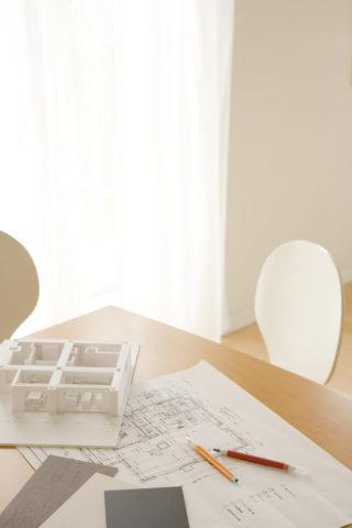 デスクの上の設計図と住宅模型