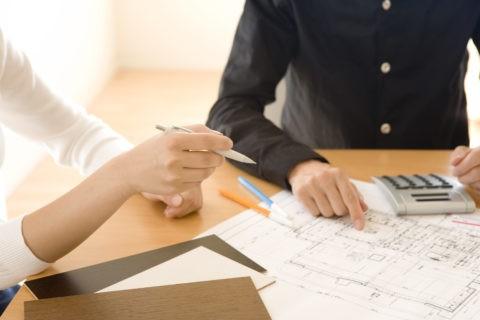 設計図を見る男性と女性の手