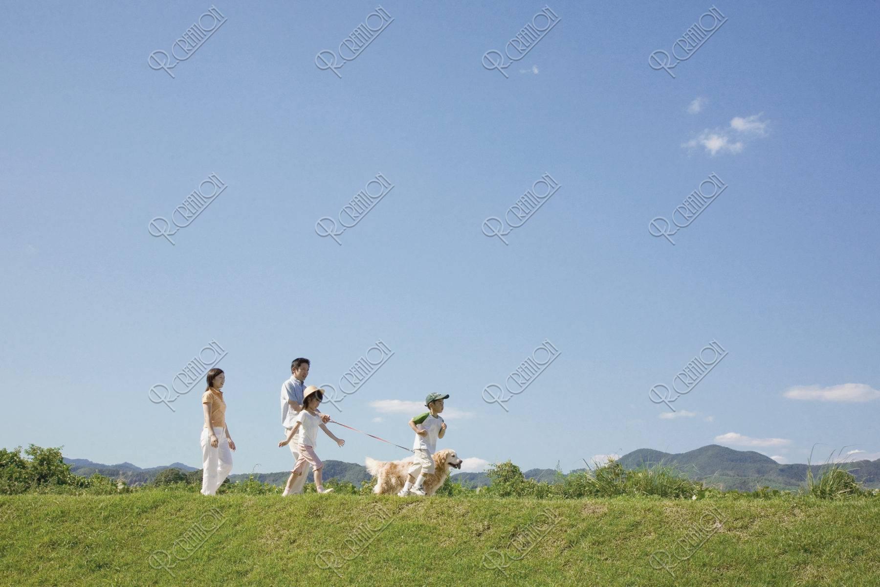 土手を散歩するファミリーと犬