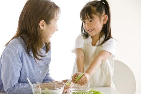 エンドウ豆をむく母と子
