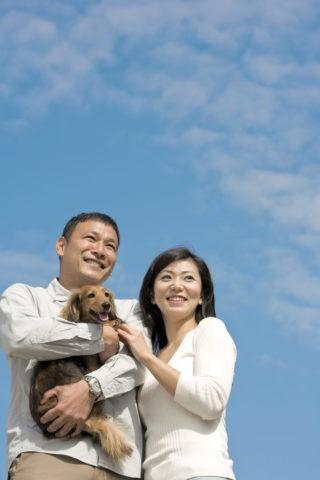 青空と犬を抱く夫婦
