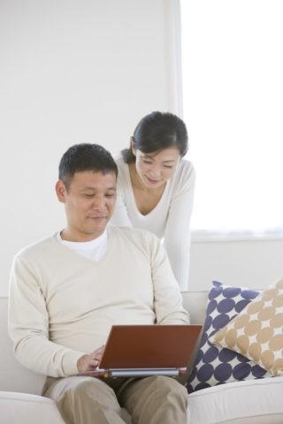 ソファでパソコンをする夫婦