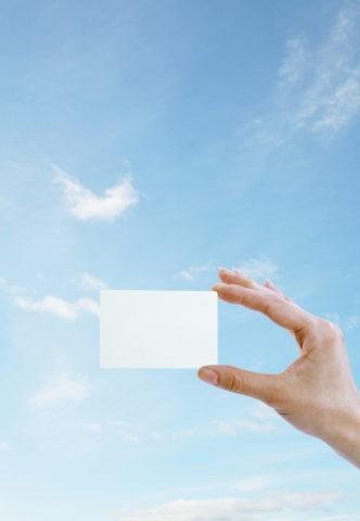 白のカードを持つ手と青空