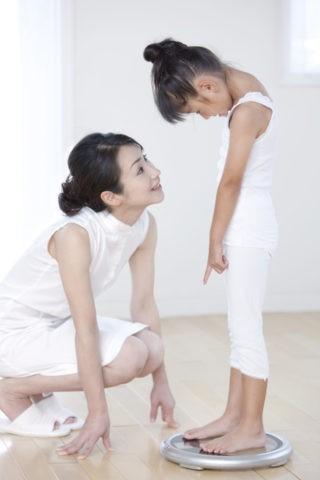 体重計に乗る娘と母