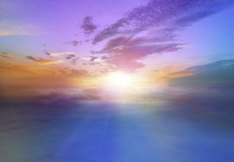 虹色の光と水平線に掛かる太陽