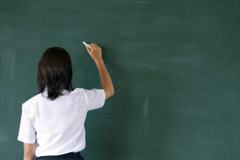 黒板に文字を書く女子高校生