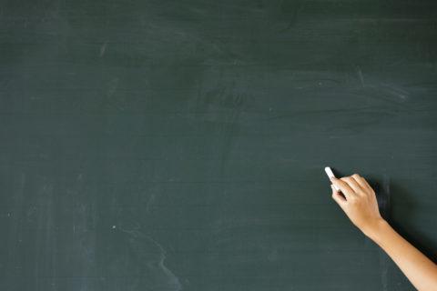 チョークで黒板に文字を書く手