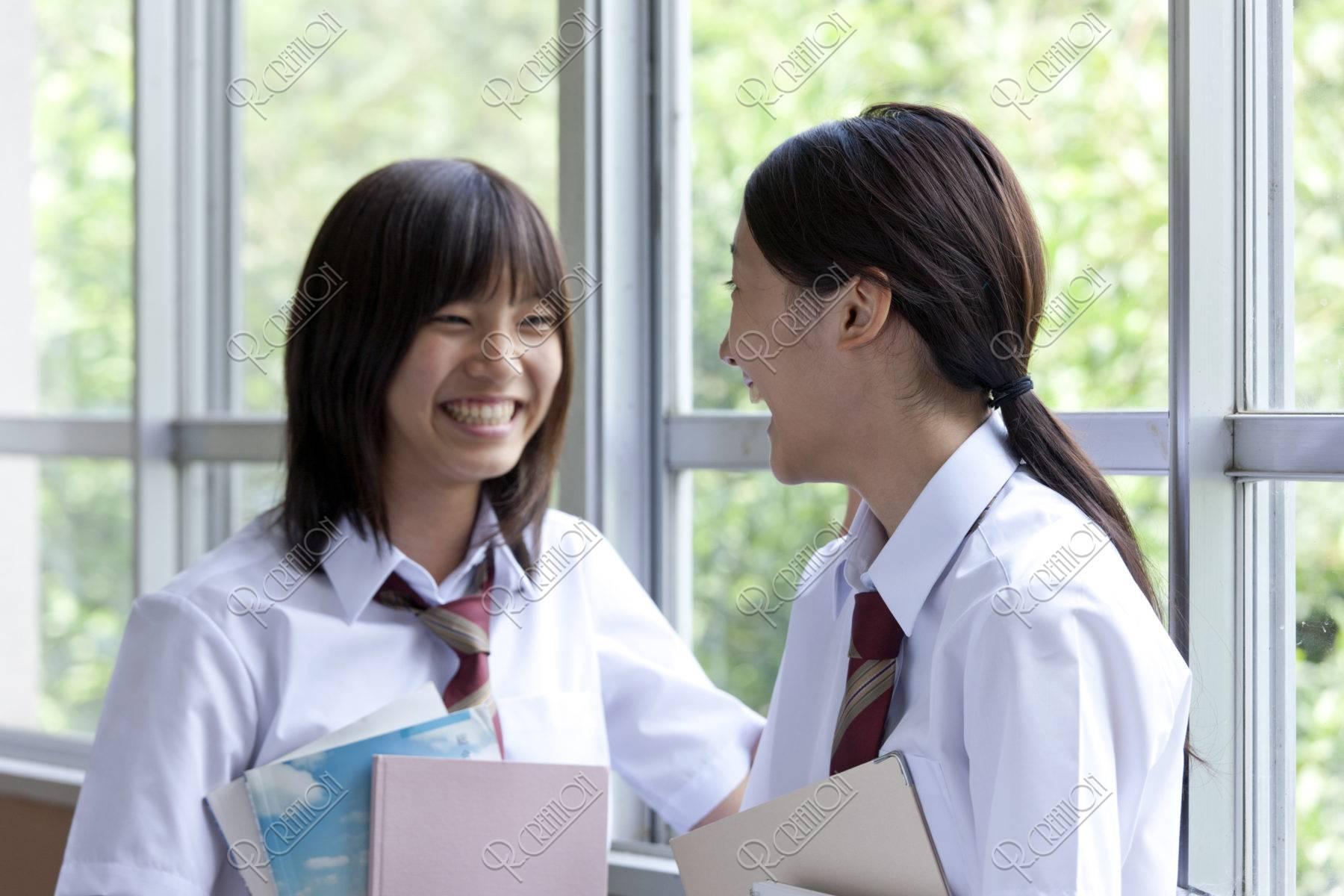 廊下でおしゃべりする女子高校生