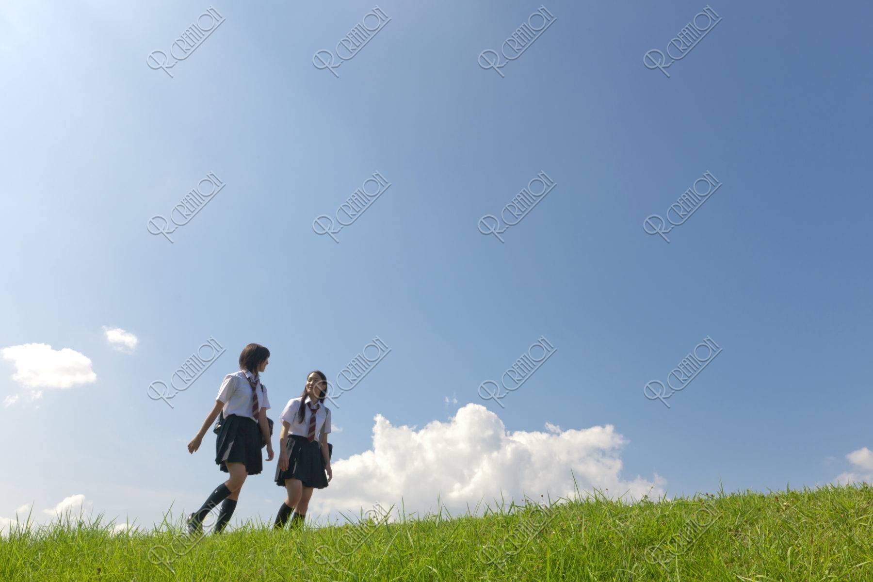 土手を歩く二人女子高校生