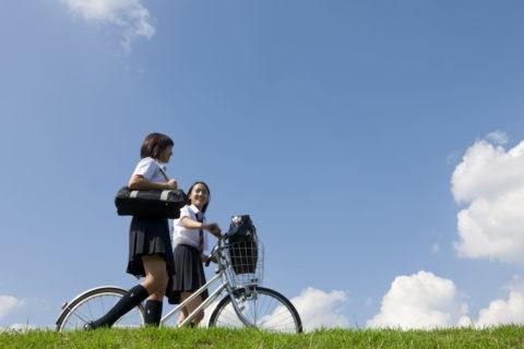 自転車を押して土手を歩く二人女子高校生