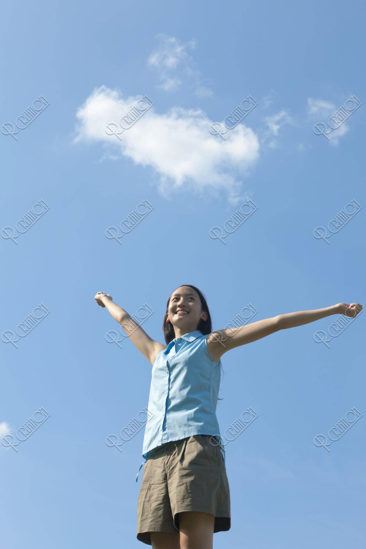 空に向かって両手を広げる10代の女の子