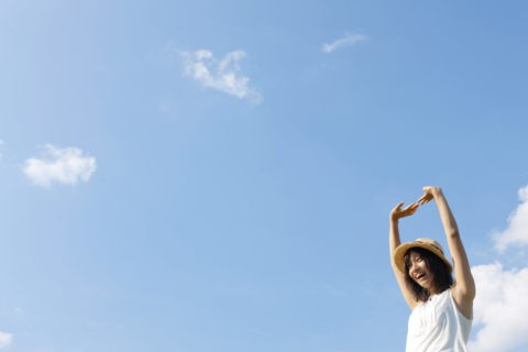 空に向かって伸びをする10代の帽子をかぶった女の子
