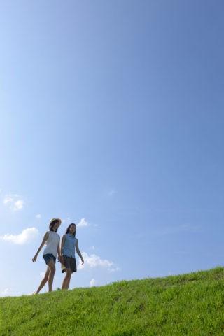 土手を歩く二人の10代の女の子
